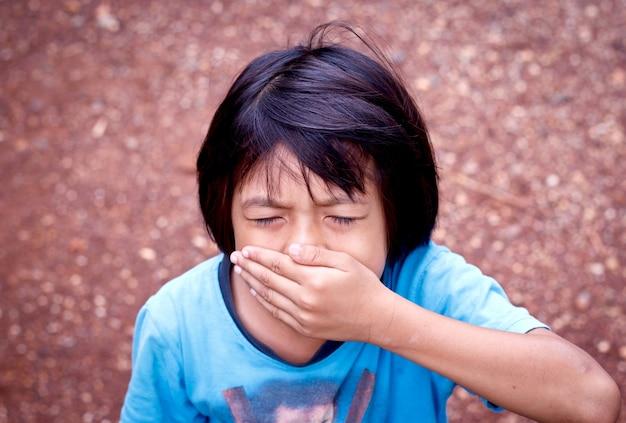 Menina cobrindo a boca com a mão.