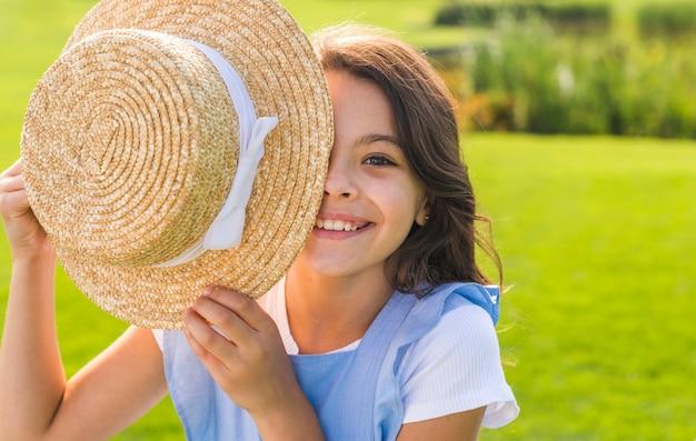Menina, cobrindo o olho com um chapéu