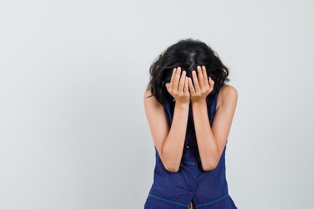 Menina cobrindo o rosto com as mãos na blusa azul e olhando triste, vista frontal.