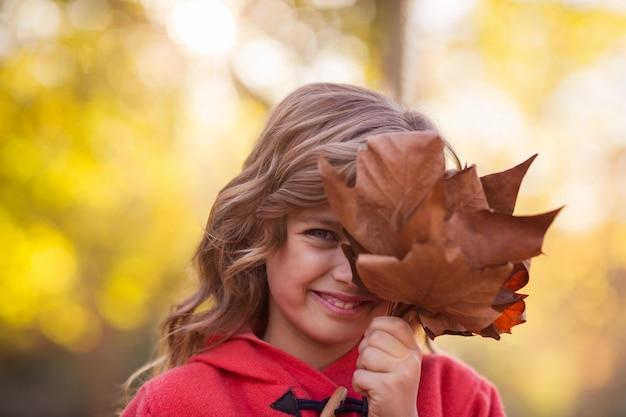 Menina, cobrindo o rosto com folhas de outono