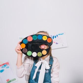 Menina, cobrindo o rosto com paleta e mostrando a língua