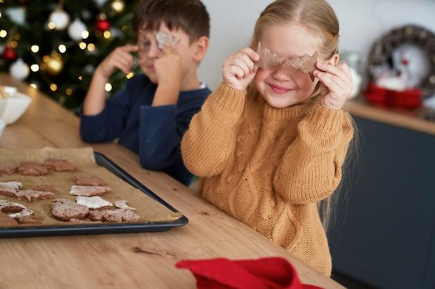 Menina cobrindo os olhos com biscoitos caseiros de gengibre