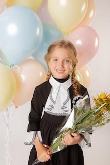 Menina colegial, aluna da primeira série com uniforme escolar em um fundo branco com bolas e flores