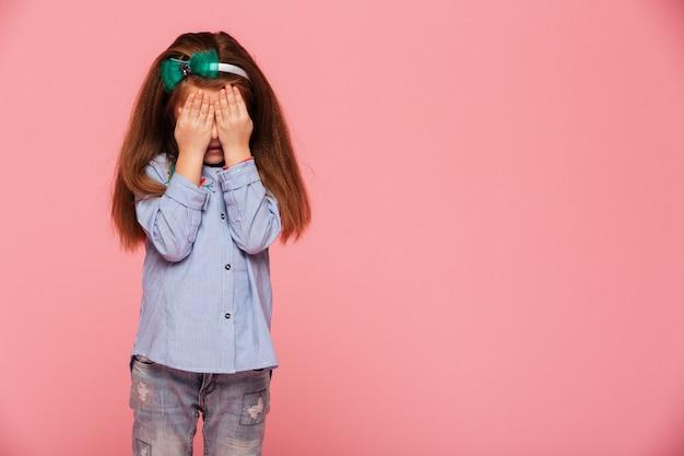 Menina colegial, cobrindo os olhos com as mãos, chorando ou tendo medo