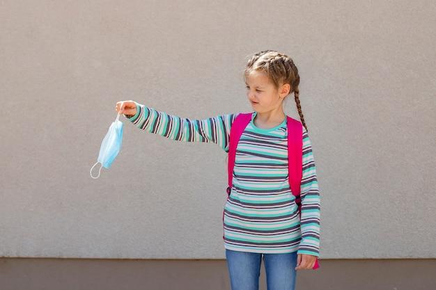 Menina colegial com mochila rosa segurando uma máscara médica na mão estendida