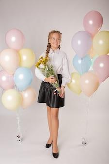 Menina colegial, estudante do ensino médio com flores e bolas em um fundo branco
