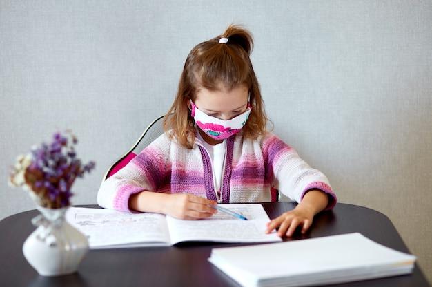 Menina colegial na máscara estudando lição de casa em casa, distância social durante o coronavírus de quarentena