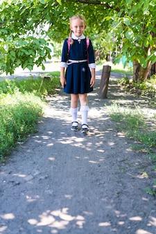 Menina colegial, vestida com um uniforme azul, com duas tranças e uma mochila rosa sobre os ombros, em meias brancas sobre fundo de outono. conceito de escola.