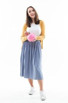 Menina coleta dinheiro em um cofrinho rosa sobre fundo branco