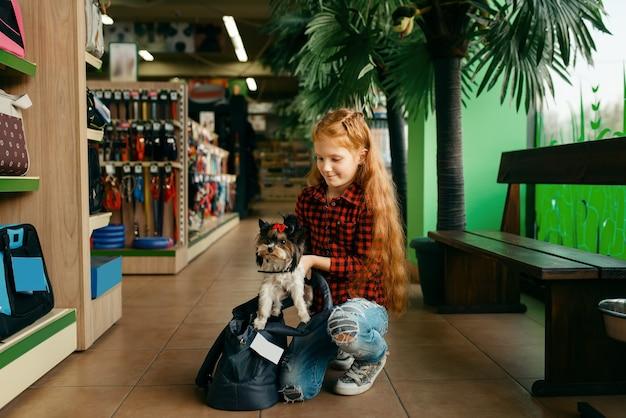 Menina coloca o cachorro na bolsa, pet shop. criança comprando equipamentos em petshop, acessórios para animais domésticos