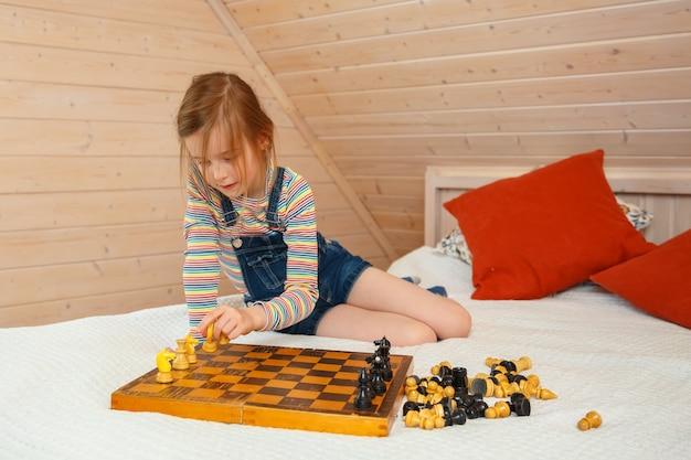 Menina coloca peças em um tabuleiro de xadrez. jogo de xadrez