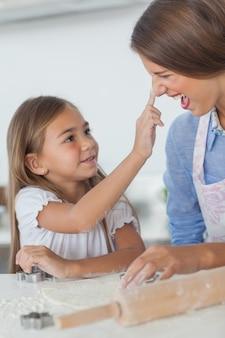 Menina colocando farinha no nariz de sua mãe