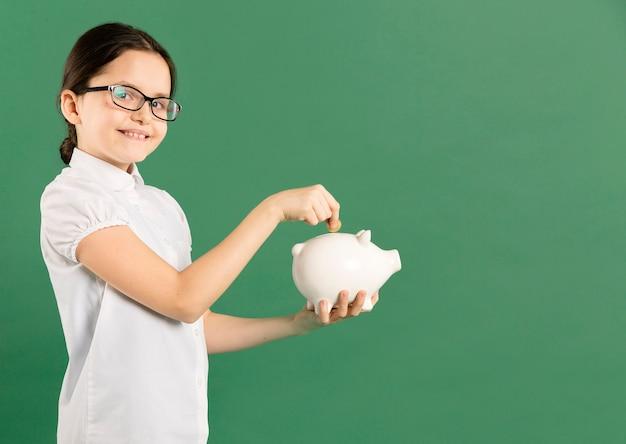Menina colocando moedas no cofrinho