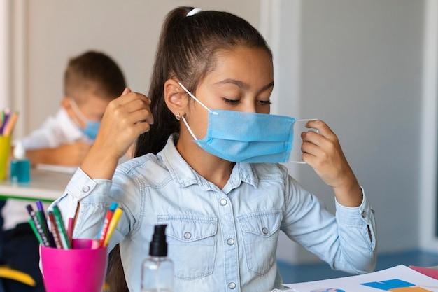 Menina colocando uma máscara facial