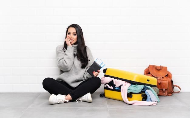 Menina colombiana viajante com uma mala cheia de roupas, sentada no chão, nervosa e assustada