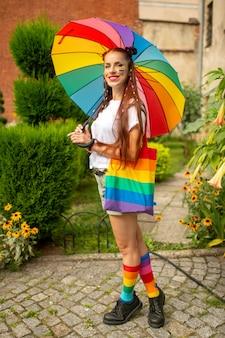 Menina colorida com acessórios lgbt posando com sorriso no rosto