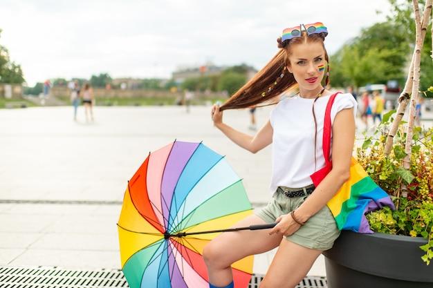 Menina colorida com bandeira lgbt pintada no rosto posando ao ar livre.