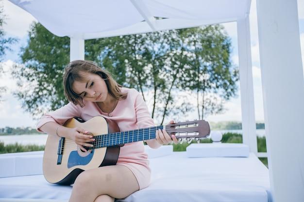 Menina com a cabeça curvada ao jogar uma guitarra