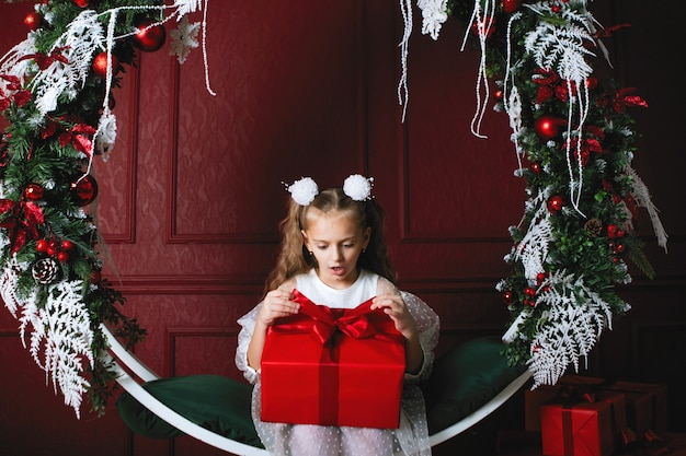 Menina com a caixa vermelha. presente de natal. adolescente se senta no balanço do arco com coroas de decoração de ano novo, ramos de abeto, bolas e guirlandas.