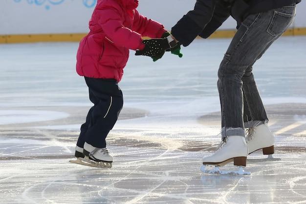 Menina com a mãe andando de skate na pista