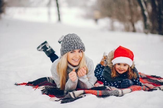 Menina com a mãe brincando em um parque de inverno