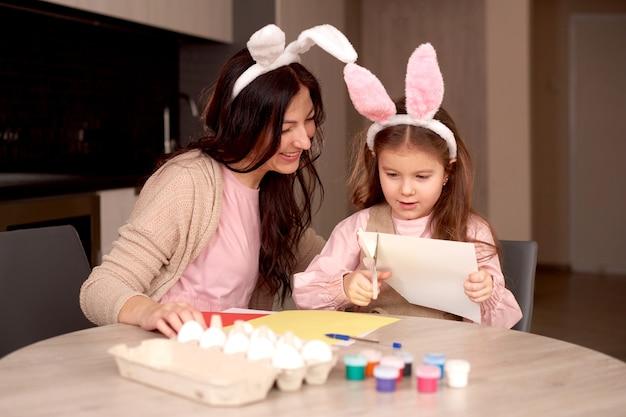 Menina com a mãe corta o coelho caseiro de papel. celebração da páscoa em casa