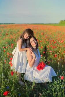 Menina com a mãe em vestidos brancos com buquê de papoulas.