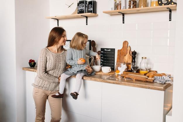 Menina com a mãe na cozinha em casa.