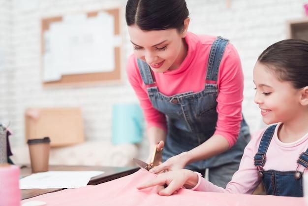 Menina com a mãe na oficina de costura