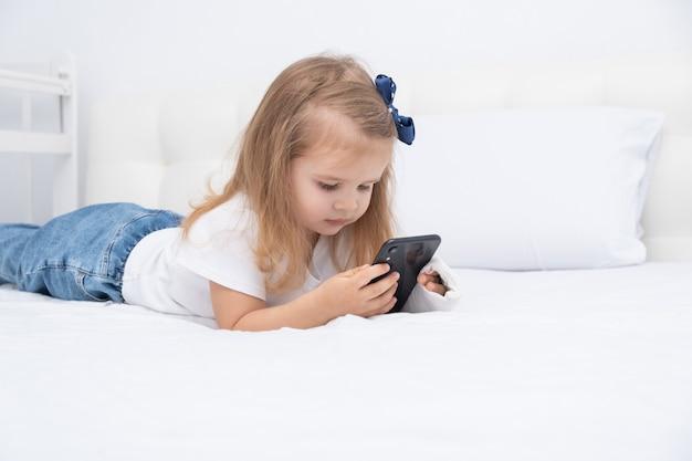 Menina com a mão engessada, deitada na cama usando o smartphone, assistindo a um desenho animado ou vídeo educacional.