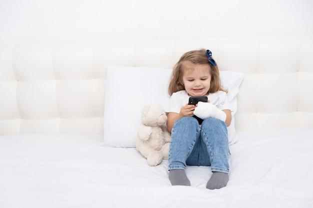 Menina com a mão engessada, sentada na cama usando o smartphone, assistindo a um desenho animado ou vídeo educacional.