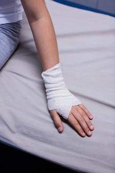 Menina com a mão machucada, sentado na cama maca