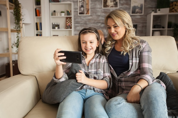 Menina com aparelho e a mãe dela em um fim de semana preguiçoso usando smartphone sentado no sofá.