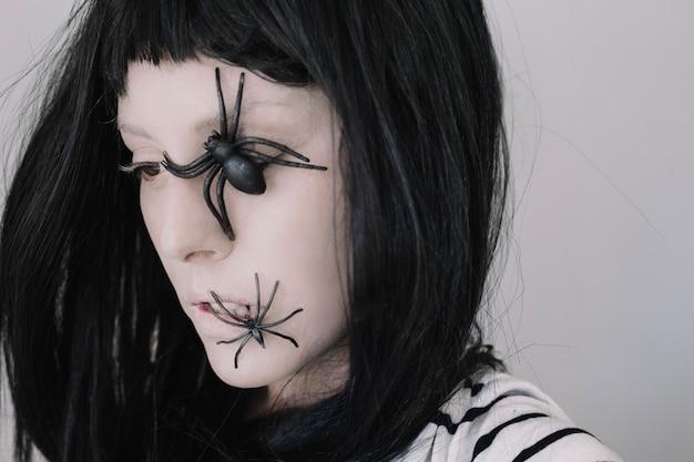 Menina com aranhas no rosto olhando para longe
