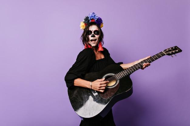 Menina com arte no rosto canta serenata e toca violão.
