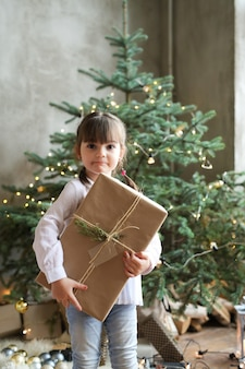 Menina com árvore de natal e presente
