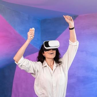 Menina com as mãos para cima usando o fone de ouvido da realidade virtual