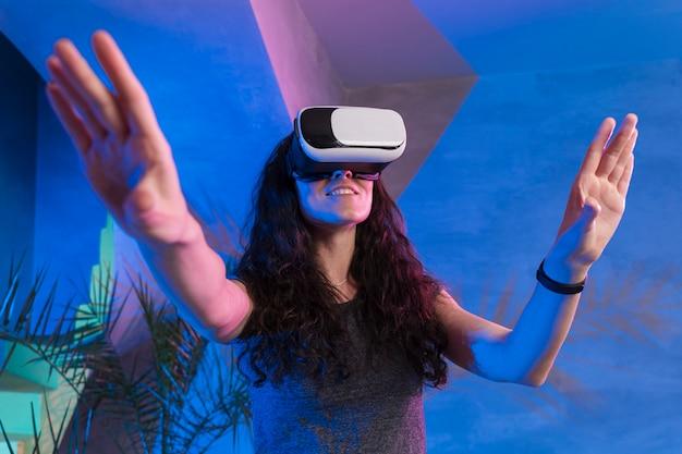 Menina com as mãos para cima usando os óculos de realidade virtual