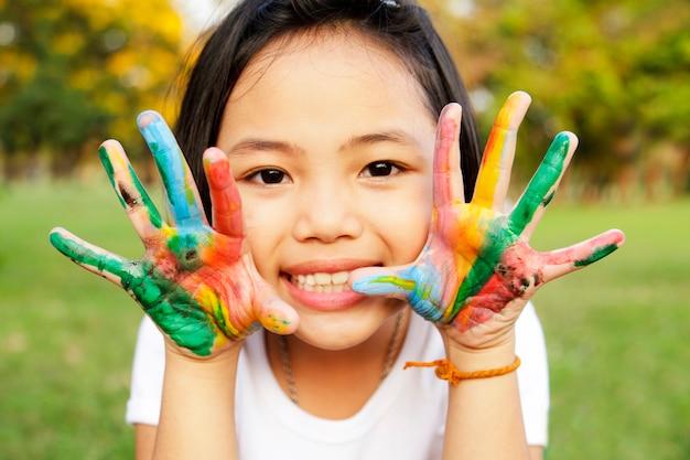 Menina com as mãos pintadas em tinta colorida