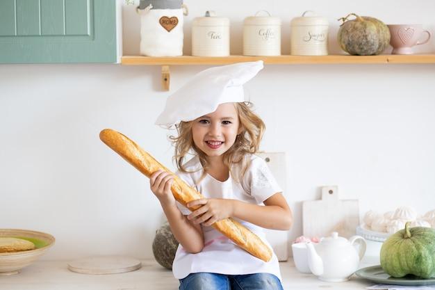 Menina com baguete fresca na cozinha em casa