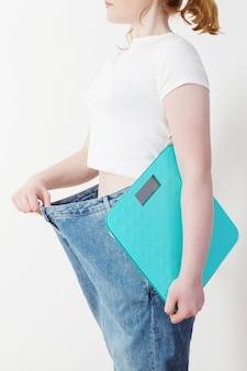 Menina com balança, puxando seus jeans grandes e mostrando a perda de peso