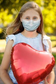 Menina com balão de coração em uma máscara médica no rosto