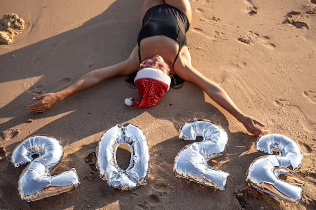 Menina com balões de prata em forma de números para o próximo ano perto do mar