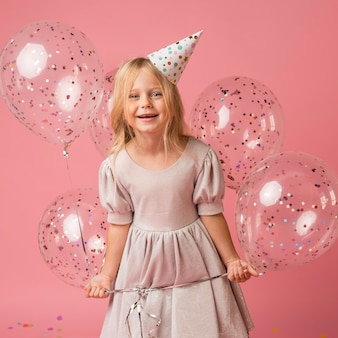 Menina com balões e chapéu de festa
