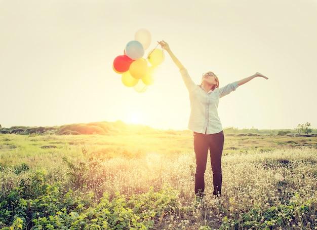 Menina com balões e os braços estendidos
