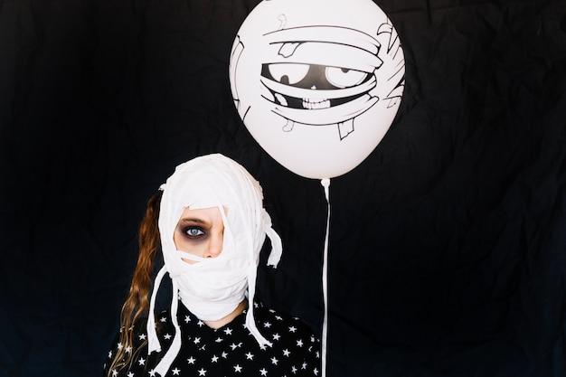 Menina com bandagens no rosto e balão