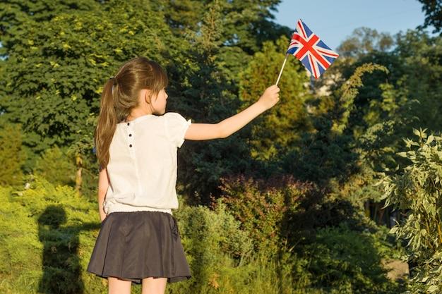 Menina com bandeira da grã-bretanha na mão, no parque ensolarado de verão