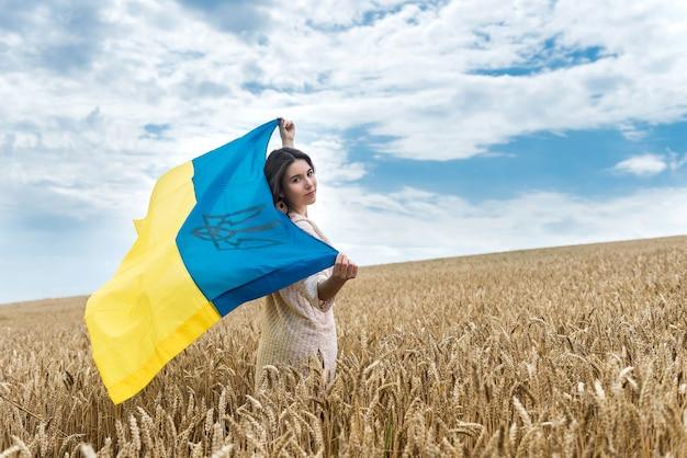 Menina com bandeira da ucrânia e atravessa um campo de trigo maduro. paz na ucrânia. aproveite o estilo de vida