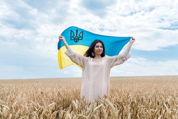 Menina com bandeira da ucrânia e caminha por um campo de trigo maduro