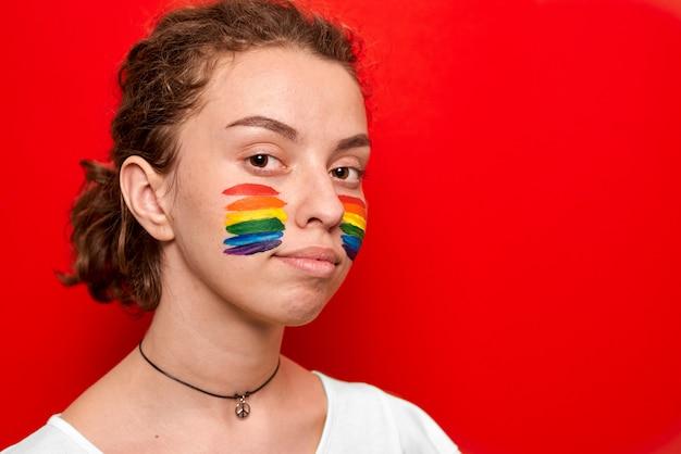 Menina, com, bandeira orgulho, pintado, ligado, dela, bochechas, sorrindo